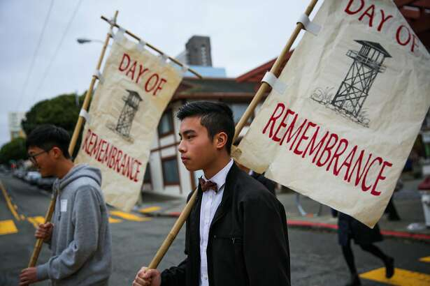 Aaron Huang (left) and Wesley Wong (right) carry banners during a procession from the Kabuki Cinema to the Japanese Cultural Center during the Remembrance of the 75th anniversary of executive order 9066 in San Francisco, California, on Sunday, Feb. 19, 2017.