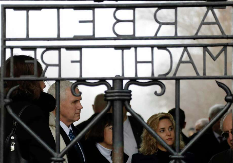 "U.S. Vice President Mike Pence, his wife Karen and his daughter Charlotte, from left, stand behind the gate with the infamous writing ""Work sets you free"" as they visit the former Nazi concentration camp in Dachau near Munich, southern Germany, Sunday, Feb. 19, 2017, one day after he attended the Munich Security Conference. (AP Photo/Matthias Schrader) Photo: Matthias Schrader, STF / Copyright 2017 The Associated Press. All rights reserved."