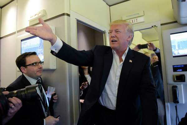 "President Donald Trump talks to reporters on board Air Force One as he arrived to speak at his ""Make America Great Again Rally"" at Orlando-Melbourne International Airport in Melbourne, Fla., Saturday, Feb. 18, 2017.  (AP Photo/Susan Walsh) ORG XMIT: FLSW115"