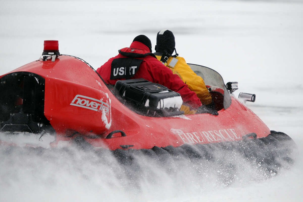 In this Feb. 13, 2017 photo, rescue crews use a hovercraft to search the frigid waters of Conesus Lake in Livonia, N.Y., for two missing snowmobilers who are believed to have fallen through the ice. Not-so-frozen lakes have claimed several snowmobilers across the Northeast so far in a relatively mild winter. (Max Schulte/Democrat & Chronicle via AP) ORG XMIT: NYROD501