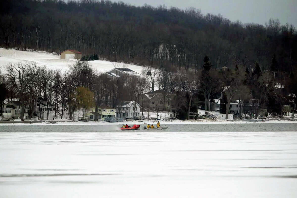 In this Feb. 13, 2017, photo, rescue crews search the frigid waters of Conesus Lake in Livonia, N.Y., for two missing snowmobilers who are believed to have fallen through the ice. Not-so-frozen lakes have claimed the lives of several snowmobilers across the Northeast so far in a relatively mild winter. (Max Schulte/Democrat & Chronicle via AP) ORG XMIT: NYROD502