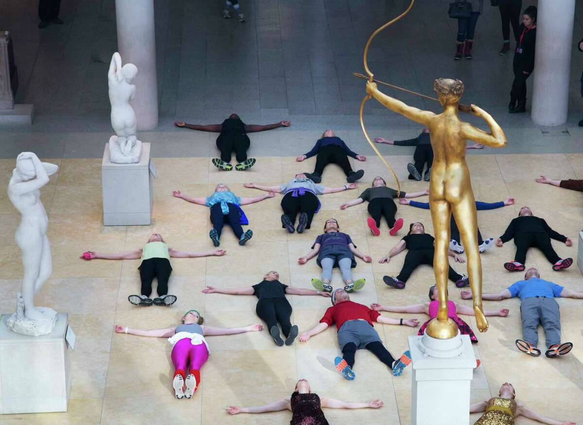 In this Feb. 10, 2017 photo, an exercise group lies down at the feet of a bronze statue of Diana, the Roman goddess of the hunt, after a workout at the Metropolitan Museum of Art in New York. The museum has been hosting lively workout sessions amid its prized masterpieces. (AP Photo/Mark Lennihan) ORG XMIT: NYML604