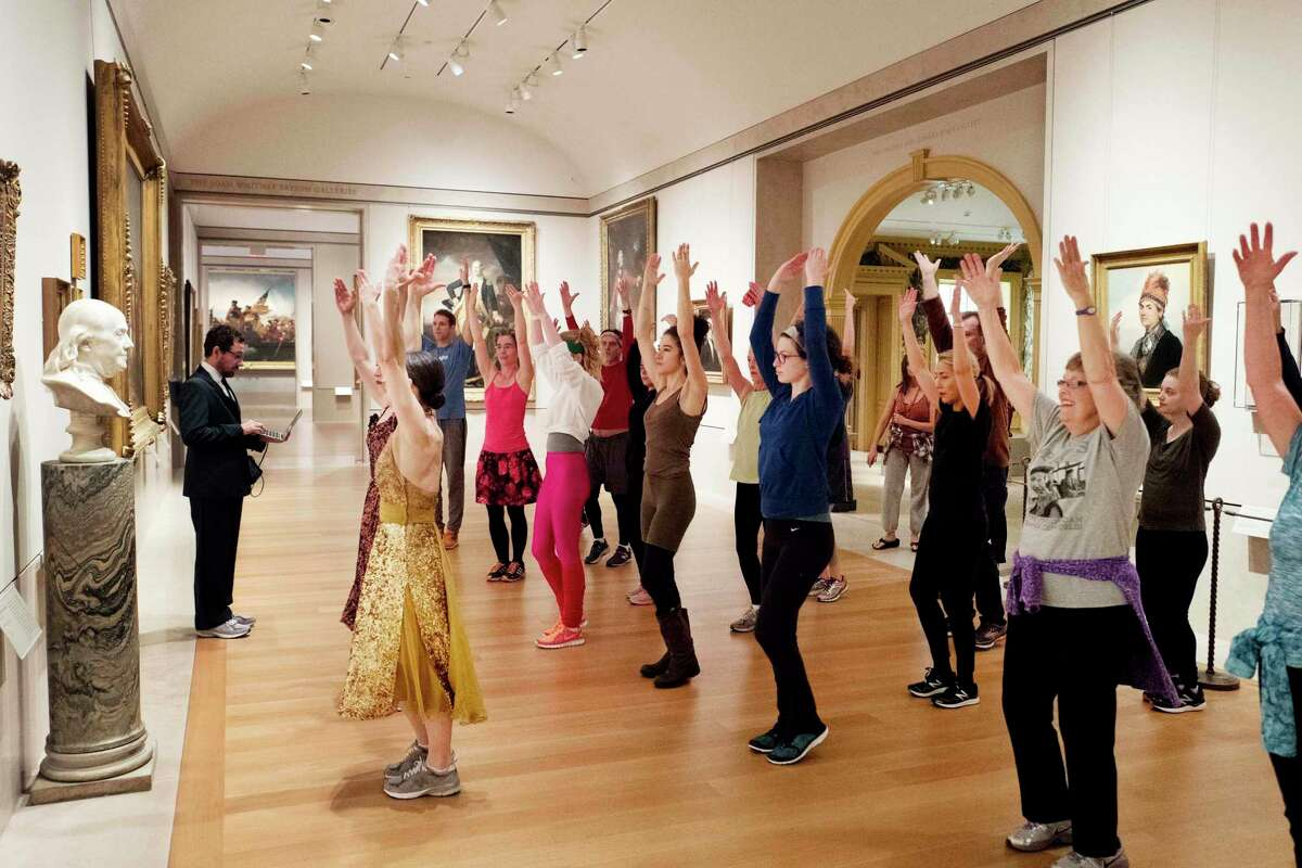In this Feb. 10, 2017 photo, an exercise group works in front of a bust of Benjamin Franklin at the Metropolitan Museum of Art in New York. New York City?'s cavernous museum has been holding lively morning workout sessions this winter amid its prized masterpieces. (AP Photo/Mark Lennihan) ORG XMIT: NYML603
