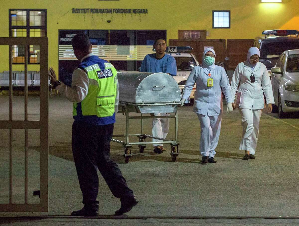 Medical staff carry a metallic bed which is used for transporting dead bodies out of the forensic department at Kuala Lumpur Hospital in Kuala Lumpur, Malaysia, Sunday, Feb. 19, 2017. Speculation that the estranged half brother of the North Korean leader was killed by two young female agents at the busy Kuala Lumpur airport last week left even the most seasoned toxicology sleuths shaking their heads. (AP Photo/Alexandra Radu) ORG XMIT: XAR101