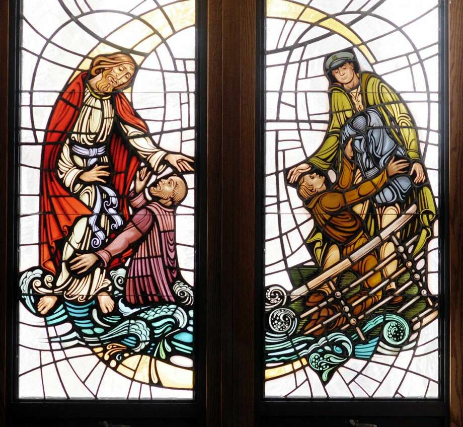 Paul Buckowski / Times Union Archive A view of a stained glass window that depicts Jesus tending to a man on the left, and Army Chaplain (1st. Lt.) Clark Poling giving his life vest to a soldier seen in the Poling Chapel at the First Reformed Church in Schenectady.