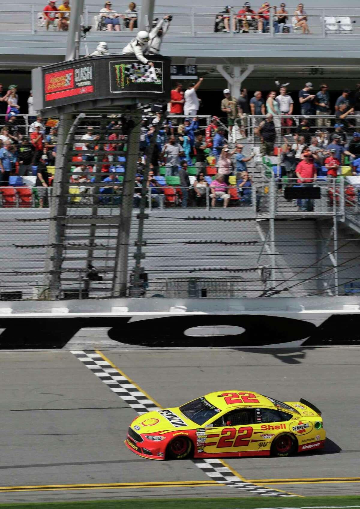 Joey Logano takes the checkered flag as he crosses the finish line to win the NASCAR Clash auto race at Daytona International Speedway, Sunday, Feb. 19, 2017, in Daytona Beach, Fla. (AP Photo/Terry Renna) ORG XMIT: DBR113