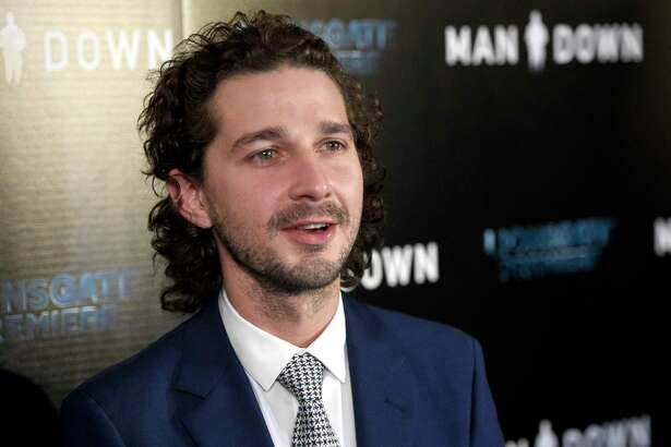 """FILE - In this Nov. 30, 2016 file photo, Shia LaBeouf arrives at the Los Angeles premiere of """"Man Down"""" at ArcLight Cinemas Hollywood. LaBeouf has brought a performance-art piece against President Donald Trump to New Mexico's largest city. The Albuquerque Journal reports that LaBeouf, along with two other artists, brought on Saturday, Feb. 18, 2017, a 24-hour live-streaming camera mounted to a wall with the message in block letters: """"He will not divide us,"""" referring to Trump. (Photo by Chris Pizzello/Invision/AP, File) ORG XMIT: CAET759"""