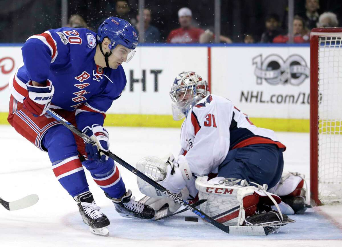 New York Rangers' Chris Kreider, left, tries to score past Washington Capitals goalie Philipp Grubauer during the second period of the NHL hockey game, Sunday, Feb. 19, 2017, in New York. (AP Photo/Seth Wenig) ORG XMIT: NYSW105