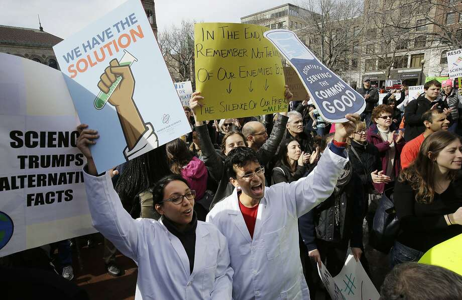 Neuroscientist Shruti Muralidhar, front left, and microbiologist Abhishek Chari, front right, hold placards and chant during a demonstration on Feb. 19, 2017, in Boston. Photo: Steven Senne, Associated Press