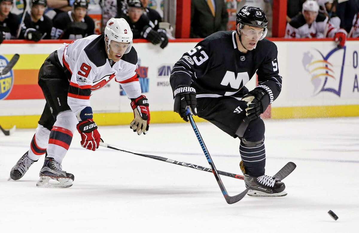 New York Islanders center Casey Cizikas (53) and New Jersey Devils left wing Taylor Hall (9) go after a loose puck during the first period of an NHL hockey game, Sunday, Feb. 19, 2017, in New York, (AP Photo/Kathy Willens) ORG XMIT: NYKW104