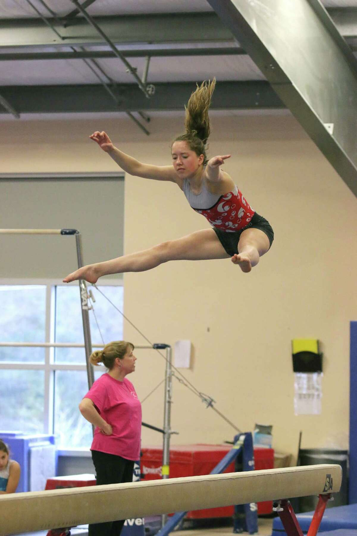 Gymnast Julia Van Horne practices on the balance beam Thursday with the Saratoga Regional YMCA Springettes at their gym in Wilton March 31, 2016. Springettes' coach Kim Hewitt stands behind. (Ed Burke/Special to The Times Union)