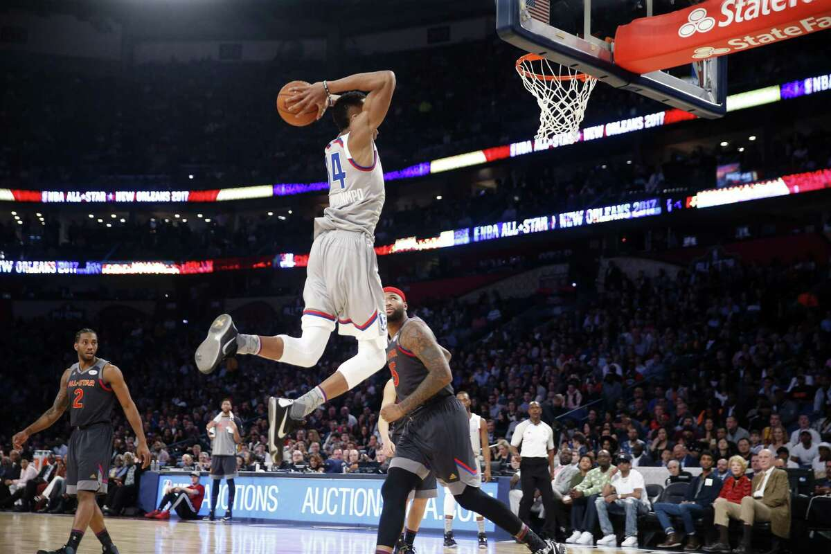 Giannis Antetokounmpo soars toward the rim as the Spurs' Kawhi Leonard (left) looks on during the first half Sunday night.