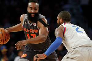Rockets guard James Harden, defended here by the Cavaliers' Kyrie Irving, was content to be a distributor Sunday night, finishing with 12 assists.