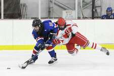 Fairfield Ludlowe/Warde's Sarah Powlishen (16), left, with the puck during a game against Greenwich.