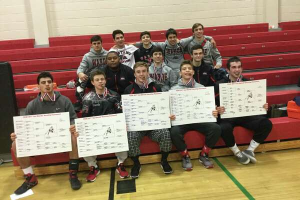 Members of the Warde wrestling team display their championship brackets and bite their medals after they won FCIAC championships on February 11. Front row from left to right: Joe Gjinaj (182), Alex Steele (132) Tim Kane (138), Izaake Zuckerman (152) and Matt Cuoco (195).