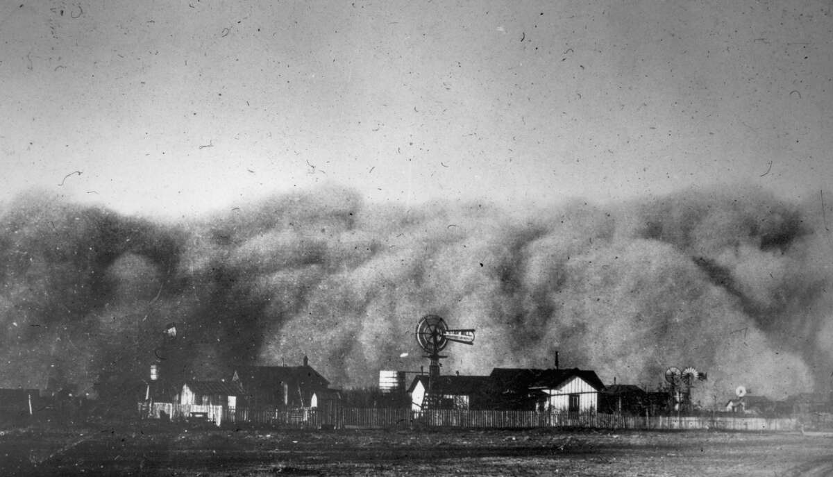 A view of dust clouds rolling over a farm on a country plain during a sandstorm, Midland, Texas in 1894.