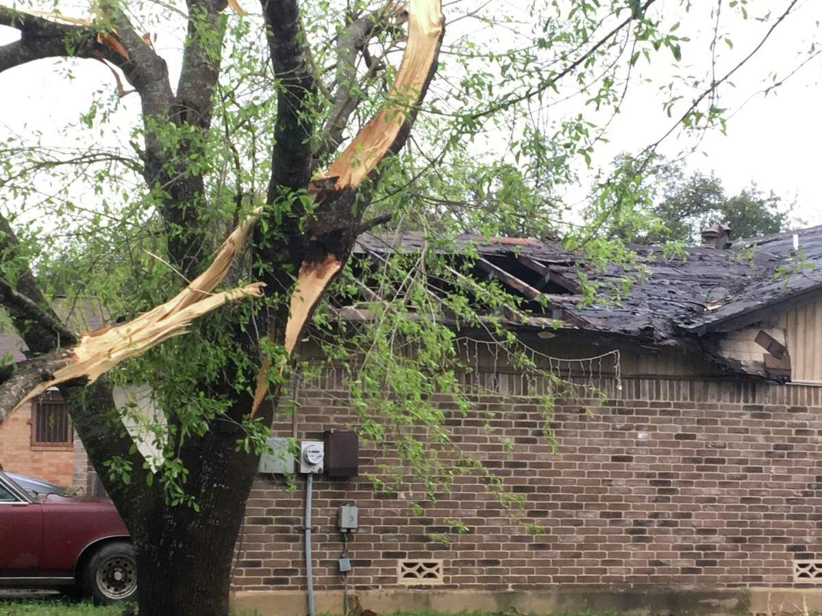 A tree split and part of a roof was torn off on this home in the 6700 block of Montgomery Drive on the Northeast Side after a strong storm swept through the area Sunday night and early Monday, Feb. 20, 2017. At least 30 homes were damaged and there were many tree limbs and other debris in the streets in the Glen and Camelot subdivisions.