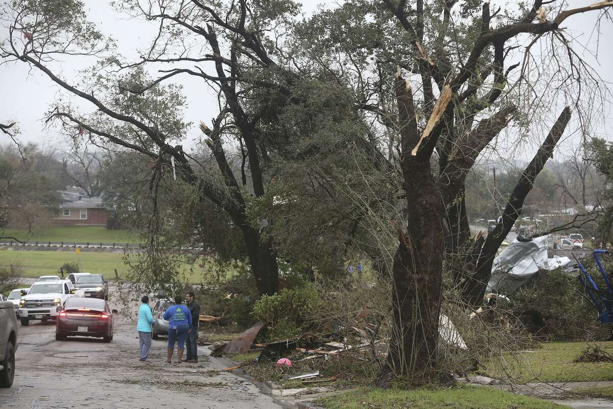 Neighbors survey damage after a storm swept through the area Sunday night February 19, 2017 on the 300 block of Sharon Drive in North Central San Antonio.