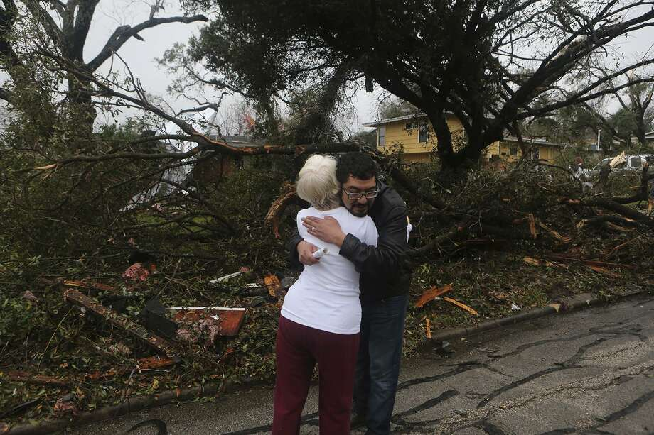 Mario Camacho (right) hugs neighbor Helen Bowen (left) after a storm swept through the area Sunday night February 19, 2017 on the 300 block of Sharon Drive. Camacho said he heard a rumbling noise at about 10:40 p.m. last night and told his daughters to hunker down in the living room as the storm hit the area. Photo: John Davenport, Staff / ©San Antonio Express-News/John Davenport