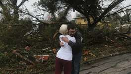 Mario Camacho (right) hugs neighbor Helen Bowen (left) after a storm swept through the area Sunday night February 19, 2017 on the 300 block of Sharon Drive. Camacho said he heard a rumbling noise at about 10:40 p.m. last night and told his daughters to hunker down in the living room as the storm hit the area.