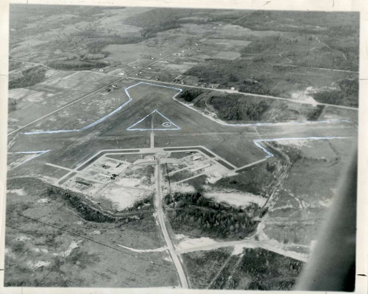 Aerial view of the Jack Barstow Airport, gives ground-bound citizens an idea of how the airport and fairground location looks. The buildings at the left center are the administration building and the flying school hangars. The white paths forming an outline close to the buildings are taxi strips, and the gray earth paths between the thin white lines (between the triangle and field outline) are plane runways. Airport Road is shown at the lower center of the picture, and the fairgrounds are on county property at the extreme right. November 1949