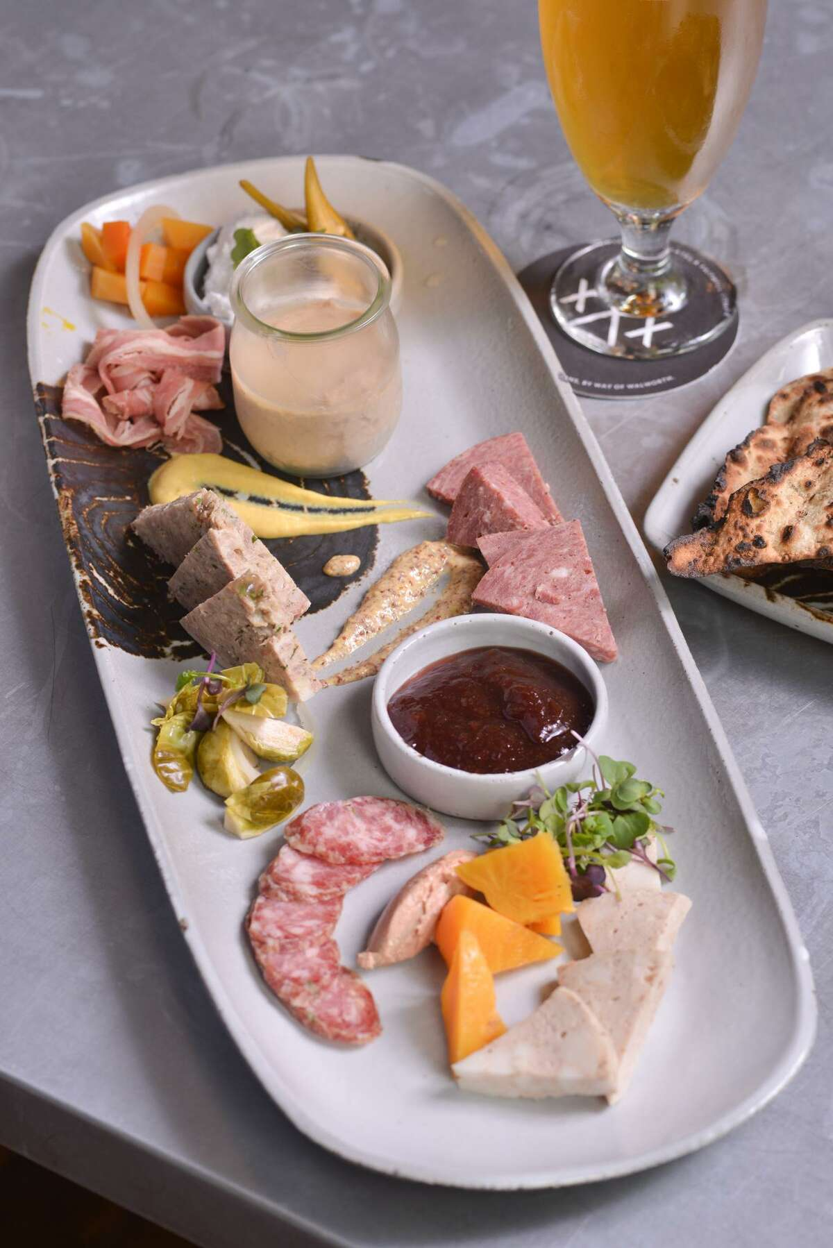 A charcuterie plate from Cured featuring mortadella, chicken liver mousse, jalapeño sauce, apple red wine jam, pickled Brussels sprouts, country style pork paté, smoked veal wurst, smoked lamb belly and whipped pork butter and beer flatbread.