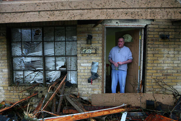 "Greg Goza stands in the doorway of his 90-year-old mother-in-law's home at 455 Linda after a tornado swept through a neighborhood in north central San Antonio Sunday night. His mother-in-law was not harmed, but the home is in shambles. ""this is what happens when mother naturr does her thing. Thank God no one got killed,"" Goza said."
