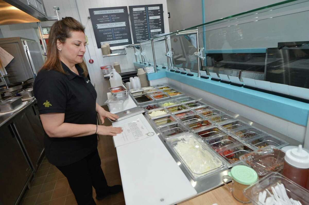 Christina Pertesis makes sure all the toppings are in the right place at the new restaurant The Simple Greek at 440 Westport Ave. in Norwalk, Conn., slated to open Tuesday, Feb. 21, 2017 as the franchisor's first Connecticut location.