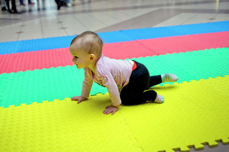 NICK KING | nking@mdn.net  10-month-old racer Willow Coleman crawls along the mat during the 2017 Diaper Derby on Saturday at the Midland Mall. The Diaper Alliance hosted the event as part of Kids Day at the Mall. Babies raced two at a time on a mat in heats to determine the champion. / Midland Daily News