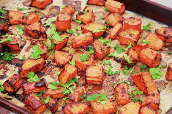 This February 2017 photo shows roasted sweet potatoes and carrots prepared with a marinade in Coronado, Calif. This dish is from a recipe by Melissa d'Arabian. (Melissa d'Arabian via AP)