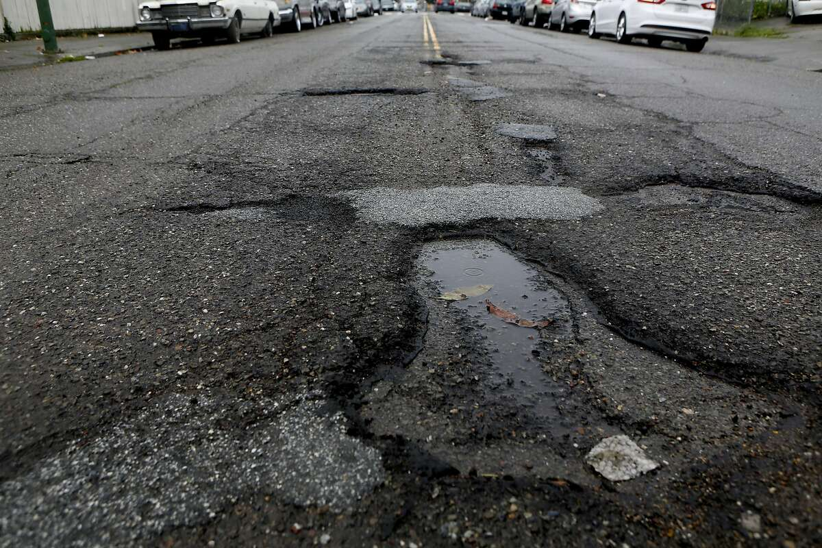Potholes are seen between East 18th Street and 10th Avenue in Oakland.