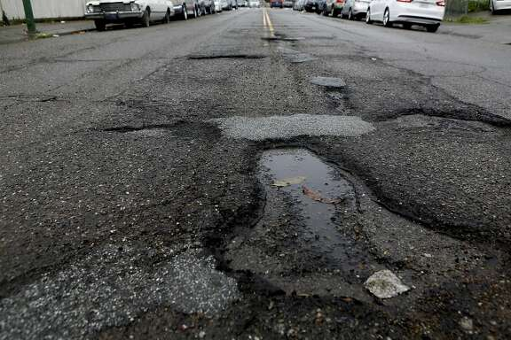 Potholes are seen between East 18th St. and 10th Ave. on Sunday, Feb. 19, 2017, in Oakland, Calif.