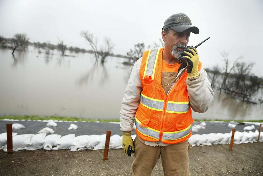 Resident Rick Hall calls in a trouble spot on the levee separating the swollen San Joaquin River from the San Joaquin River Club in Tracy, Calif., on Sunday, February 20, 2017. Photo: Scott Strazzante, The Chronicle