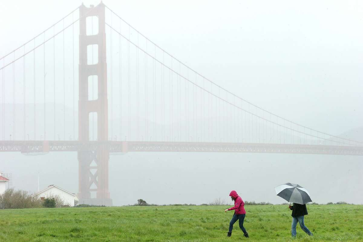 From right: Nathaniel Fleming and Emily Nahem take a stroll at Crissy Field during a storm on Monday, Feb. 20, 2017, in San Francisco, Calif. The National Weather Service announced flood, snow and wind advisories throughout the upper half of California.