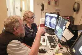 MRI technician Mindy Dixon and Stephen Dager (left) review brain scans in order to better understand the child's brain chemistry.