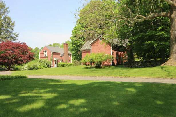 The four-acre sub-dividable property at 2031 Redding Road features a large red barn and a red guest house that was converted from its original barn structure. The guest house generates income and the barn could be used again for animals.