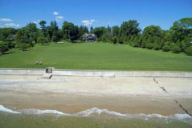 This 7.7-acre Gold Coast gated property at 114 Beachside Avenue comprises an 8,482-square-foot main house, carriage house, 365 feet of water frontage, and a private beach on Long Island Sound.