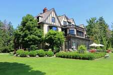 The Elizabethan Tudor-style colonial at 114 Beachside Avenue in the Greens Farms neighborhood features decorative details throughout including on the stucco and timbered exterior. Above the front entrance is a hand-carved lintel depicting the traditional Tudor rose.
