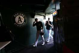 Members of the Oakland Athletics' head to their clubhouse after batting practice before playing the Houston Astros in MLB game at O.co Coliseum in Oakland, Calif. on Tuesday, July 22, 2014.