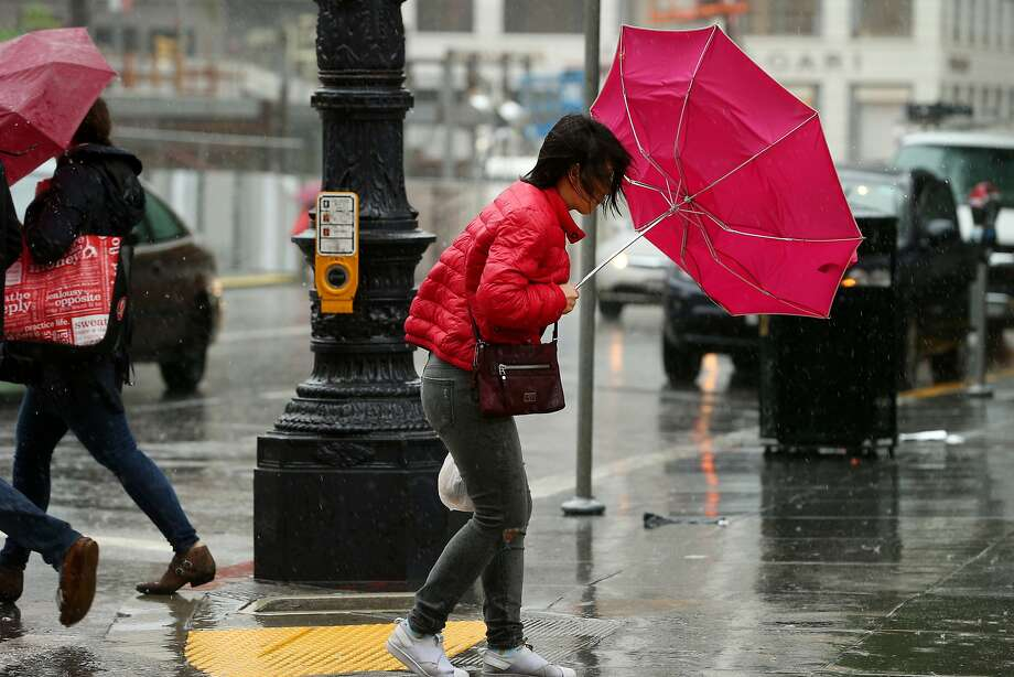 A storm system moving into Northern California is expected to bring high winds to the Bay Area Thursay and Friday. In this photo, Qian Sun's umbrella flips downtown during a storm on Monday, Feb. 20, 2017, in San Francisco, Calif.  Photo: Santiago Mejia, The Chronicle