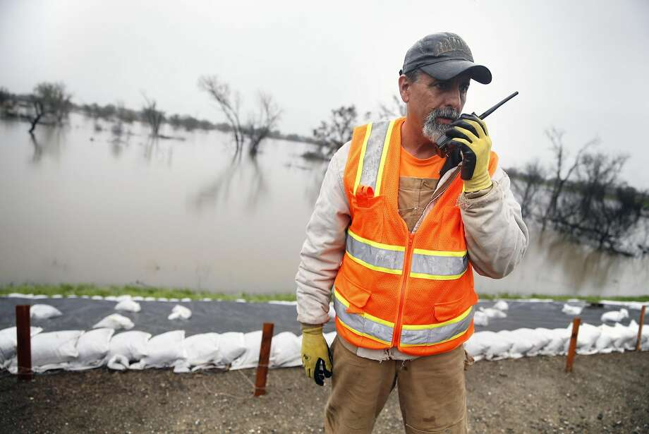 Resident Rick Hall calls in a trouble spot on the levee separating the swollen San Joaquin River from the San Joaquin River Club in Tracy. Photo: Scott Strazzante, The Chronicle