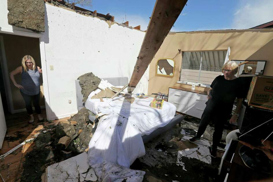 Mikela Kinnison (left) and her mother Ilona show the damage to the bedroom at Kinnison's home, in the 300 block of Burnside Drive, after tornadoes moved through the area late Sunday night.
