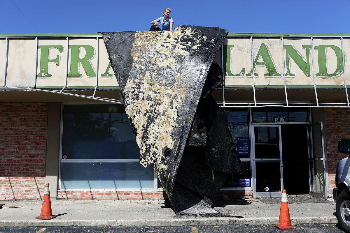 Jennifer Dean with PuroClean works to dislodge part of the roof that was blown off a Goodwill Donation Station at the corner of Nacogdoches and North New Braunfels roads in Alamo Heights on Monday, Feb. 20, 2017.