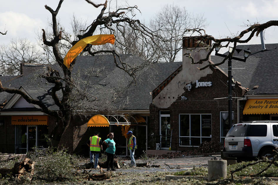 People survey the storm damage at the Carousel Court Shopping Center at the corner of Nacogdoches and North New Braunfels roads in Alamo Heights on Monday, Feb. 20, 2017.