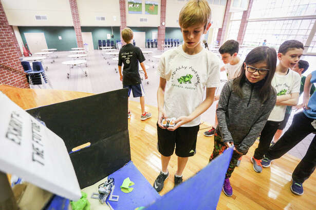Vi Nguyen and Andres Mouritsen, members of the Mitchell Intermediate Lego League Robotics team, explain the stages of their TOADally Awesome project, an idea to help save the endangered Houston toad, on Friday, Feb. 17, 2017, at Mitchell Intermediate.