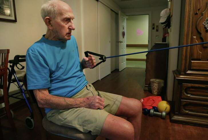 Robert Udclaire, who turns 98 on Feb. 17, works out with physical trainer Anthony Rodriguez in his apartment at the Chandler Assisted Living complex on Monday, Feb. 13, 2017.
