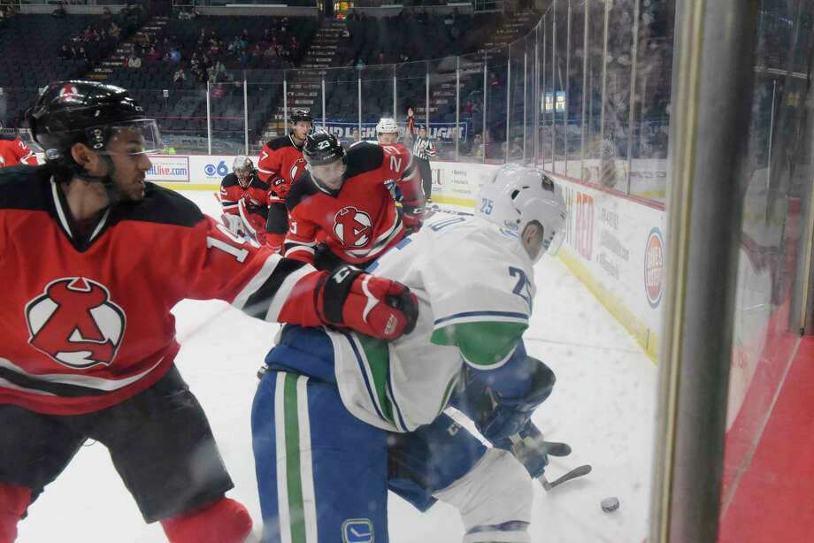 Albany Devils Brian Gibbons, left, and Vojtech Mozik attempt to get the puck away from Utica Comets Darren Archibald during their game on Monday, Feb. 20, 2017, in Albany, N.Y.   (Paul Buckowski / Times Union) Photo: PAUL BUCKOWSKI / 20039355A