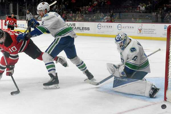 Albany Devils Rod Pelley, left, takes a shot on goal as Utica Comets David Shields, center, and goalie Richard Bachman defend during their game on Monday, Feb. 20, 2017, in Albany, N.Y.   (Paul Buckowski / Times Union)