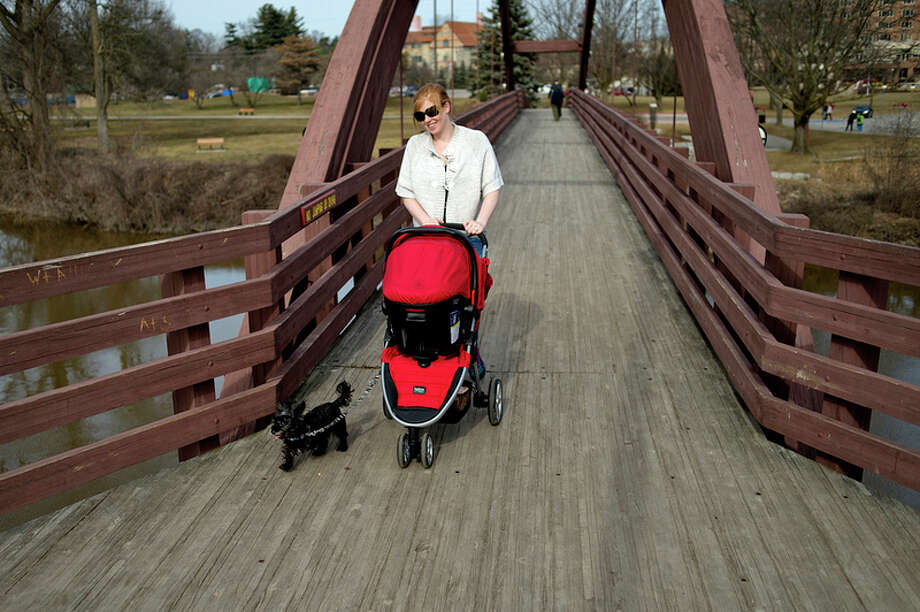 NICK KING | nking@mdn.net  Pushing her 1-month-old daughter Emma and walking her dog Roxy, Michelle Krueger takes a stroll over the Tridge during an unseasonably warm Monday in Midland. Krueger said that they were all excited to be outside, especially Roxy. / Midland Daily News