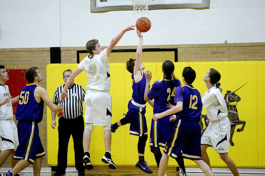 Bullock Creek's Scott Spica, left, blocks a shot by Bay City Central's Spencer Moulthrop during the first half on Monday at Bullock Creek High School. Photo: NICK KING   Nking@mdn.net